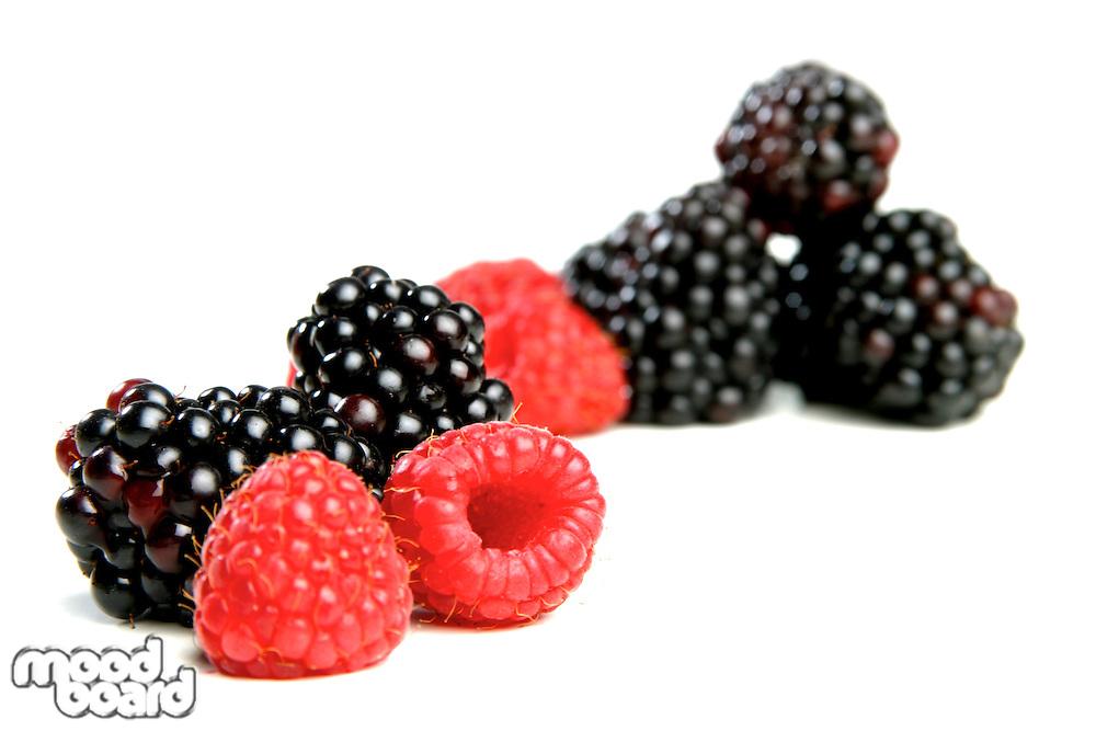 Raspberries and blackberries on white background
