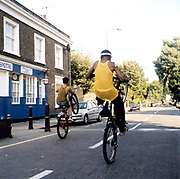 Two teenage boys doing wheelies on their bikes.