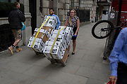 Clerks push awkward trolleys of legal documents across the road from the High Court on Fleet Street, on 17th October 2017, in the City of London, England.
