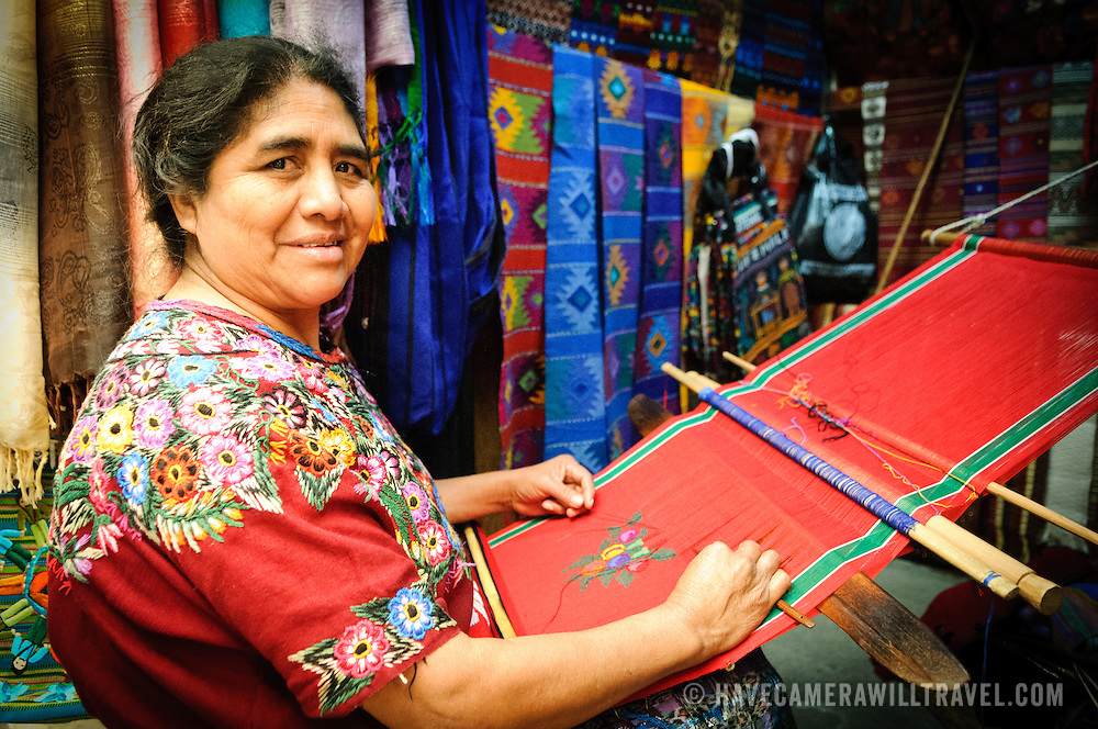 A Maya woman using a backstrap loom to weave a Christmas-themed decorative textile in a market in Antigua, Guatemala.