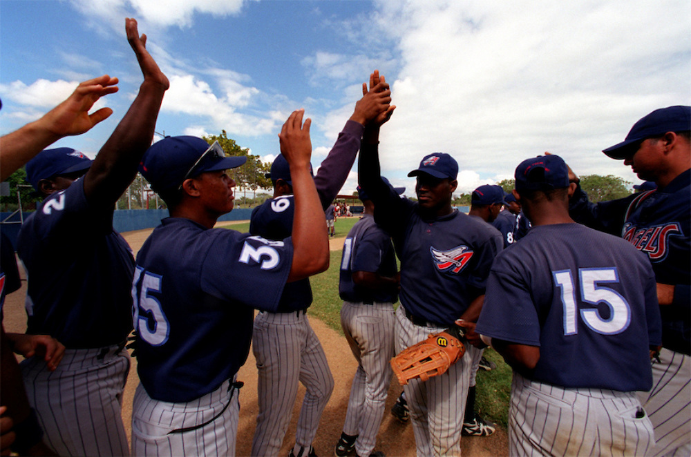 024222.SP.0114.angels10.kc--San Pedro de Macoris, Dominican Republic--Players exchange 'hi-fives' after a day game between the Anaheim Angels Academy Team and the Boston Red Sox Academy Team. At a young age Dominican boys learn that baseball could be their chance to make it in the big leagues. The little league baseball system is mostly disorganized but the baseball academies run by MLB teams provides an all around learning experience for boys once they reach sixteen.