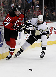 Dec 30, 2009; Newark, NJ, USA; New Jersey Devils right wing Niclas Bergfors (18) and Pittsburgh Penguins defenseman Sergei Gonchar (55) fight for a loose puck during the second period at the Prudential Center.