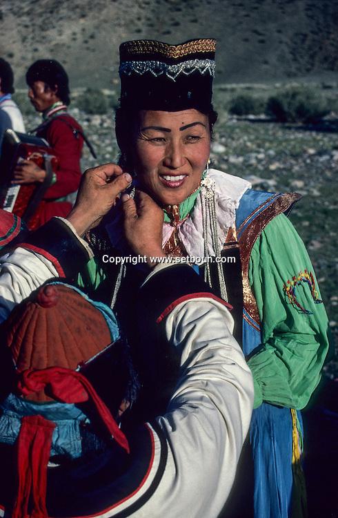 Mongolia. Getting ready for a concert. In the improvised wings of an open air  - theatre - , a singer dressed in the traditional Zaqtchin Mongol dress is assisted as she dons her long silver earrings before going on stage (Manqan, in the aymag of Qovd). In the Altay mountain region in western Monglia, many small Mongolian ethnic groups live side by side.  The Zaqtchins, with their curious traditional dress, are one of them.  This outfit - reserved for important occasions - can also be used as stage dress for the local artists.   / Préparation au concert. (Sum de Mangan, dans aymag de Qovd, Mongolie). Dans une sorte de coulisses improvisées en plein air cette chanteuse, revêtue d'un costume traditionnel typique des Mongols zaqtchin, se fait aider à mettre ses longues boucles d'oreille en argent ciselé, avant d'entrer en scène. ( Chanteuse en costume zaqtchin. Dans la région de la chaîne de l'Altay à l'ouest de la Mongolie, une mosaïque de petites ethnies mongoles coexistent, dont les zaqtchin au costume singulier. Porté uniquement aux grandes occasions de fête, cet ensemble peut aussi servir de tenue de scène pour les artistes originaires de l'endroit.