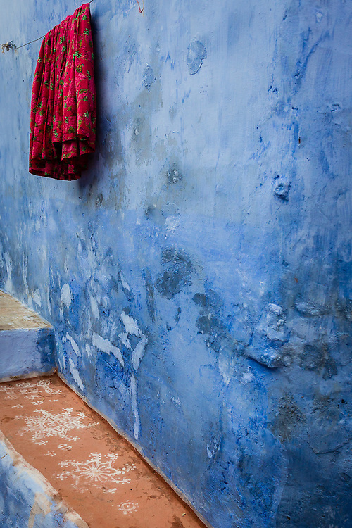 A red sari hangs on a clothesline, contrasting with the blue wall behind.
