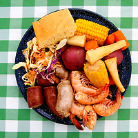 LITTLE ST. SIMONS ISLAND, FL -- October 2, 2010 -- An outdoor picnic meal of fresh Georgia shrimp, sausage, veggies, potatoes, slaw, cornbread is served on a beach to guests on Little St. Simons Island on Saturday, October 2, 2010.   The 10,000 acres of marshland, beaches, and forests are a refuge for wildlife and vacationers alike with only 32 guests permitted a night.  (Chip Litherland for Bay Magazine)