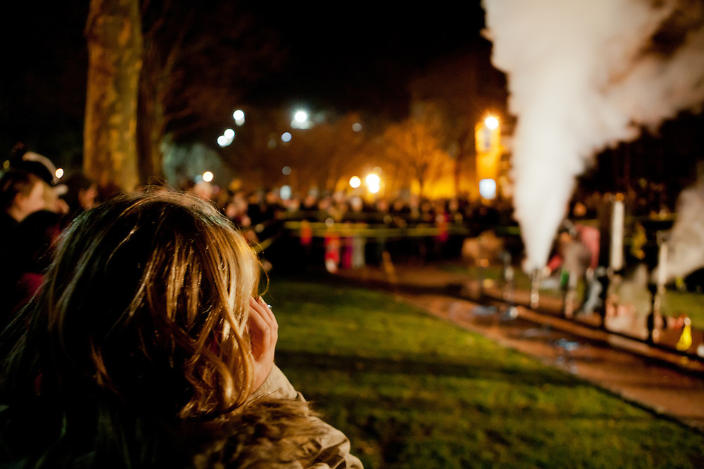 A spectator covers her ears against the deafening sound of the whistles.