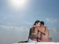 Young couple embracing on cushions outdoors back view