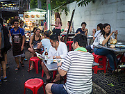 26 MAY 2015 - BANGKOK, THAILAND: People eat on the sidewalk on Sukhumvit Soi 38, one of the most famous street food areas in Bangkok. The food carts and small restaurants along the street have been popular with tourists and Thais alike for more than 40 years. The family that owns the land along the soi recently decided to sell to a condominium developer and not renew the restaurant owners' leases. More than 40 restaurants and food carts will have to close. The first wave of closings could start as soon June 21 and all of the restaurants are supposed to close over the next several months.     PHOTO BY JACK KURTZ