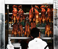 Peking ducks hang in a window display in Shenzhen.