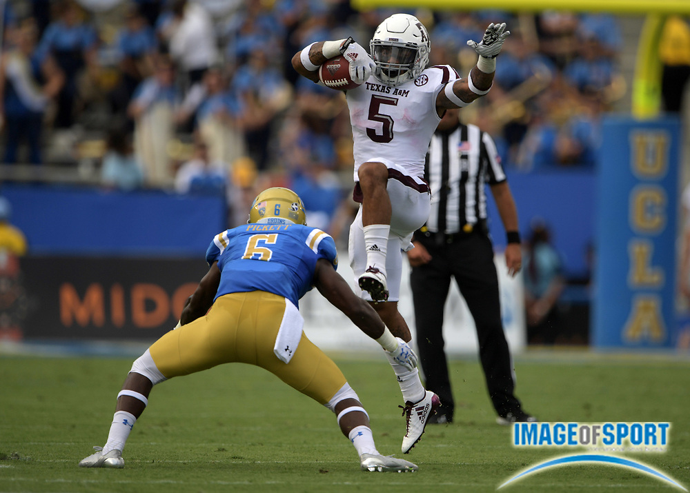 Sep 3, 2017; Pasadena, CA, USA; Texas A&M Aggies running back Trayveon Williams (5) hurdles UCLA Bruins defensive back Adarius Pickett (6) during a NCAA football game at Rose Bowl.