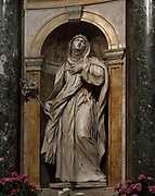 Statue of St Catherine of Siena, by Ercole Ferrata, 1610-86, in the Chapel of the Madonna del Voto, in the Duomo di Siena or Siena Cathedral, built 1196-1348 and consecrated in 1215, designed by Giovanni di Agostino, Giovanni Pisano and Camaino di Crescentino, in Siena, Tuscany, Italy. The cathedral has elements of Italian Gothic, Romanesque, and Classical styes and is built from stripes of white and green-black marble. The historic centre of Siena is listed as a UNESCO World Heritage Site. Picture by Manuel Cohen