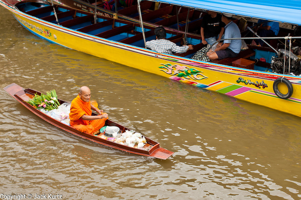 """10 JULY 2011 - AMPHAWA, SAMUT SONGKRAM, THAILAND:    A Buddhist monk from Wat Amphawan Chetiyaram in Amphawa, Thailand, about 90 minutes south of Bangkok, paddles past a water taxi down the main canal during his alms round. Most of the monks from the temple use boats to go from house to house on their alms rounds. The Thai countryside south of Bangkok is crisscrossed with canals, some large enough to accommodate small commercial boats and small barges, some barely large enough for a small canoe. People who live near the canals use them for everything from domestic water to transportation and fishing. Some, like the canals in Amphawa and nearby Damnoensaduak (also spelled Damnoen Saduak) are also relatively famous for their """"floating markets"""" where vendors set up their canoes and boats as floating shops.     PHOTO BY JACK KURTZ"""