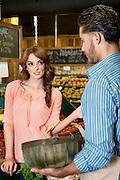 Woman looking at store clerk in supermarket