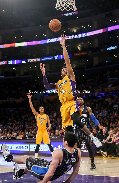 Orlando Magic forward Ehsan Ilyasva, bottom,  falls to the court as Los Angeles Lakers guard D'Angelo Russell going up for shoot during the second half of an NBA basketball game Tuesday, March 8, 2016, in Los Angeles.  Lakers won 107-98. (AP Photo/Ringo H.W. Chiu)