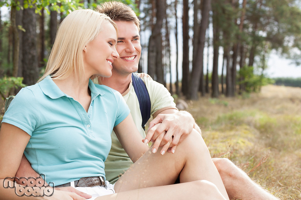 Loving hiking couple smiling while relaxing in forest