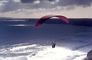 A man paragliding off a cliff over the sea, UK 2004