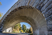 A handsome stone bridge of the Blue Ridge Parkway (Milepost 45.6) crosses over US-60 (which goes west to Buena Vista & Lexington and east to Amherst) in Virginia, USA. Notice the white stalactites forming under the old arched stones. The scenic 469-mile Blue Ridge Parkway was built 1935-1987 to aesthetically connect Shenandoah National Park (in Virginia) with Great Smoky Mountains National Park in North Carolina, following crestlines and the Appalachian Trail. The Parkway is carried across streams, railway ravines and cross roads by 168 bridges and six viaducts. The Blue Ridge Mountains are a subset of the Appalachian Mountains.