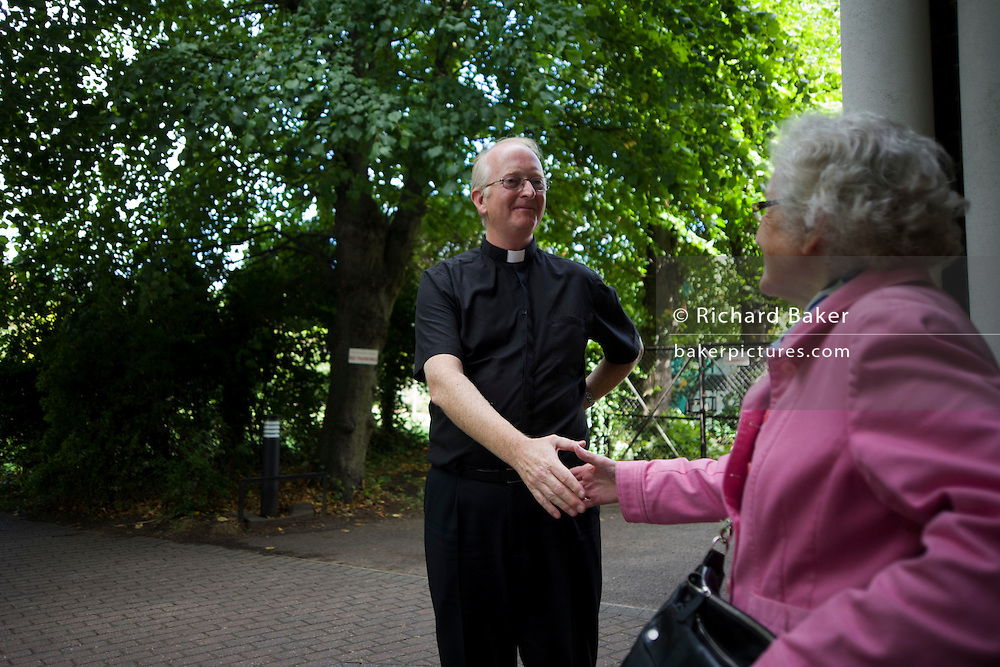 Catholic priest bids goodbye to parishioner after morning Mass at St. Lawrence's Catholic church in Feltham, London.