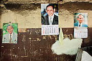 "Mar. 21, 2009 -- BANGKOK, THAILAND: Photos of His Majesty King Bhumibol Adulyadej of Thailand on a wall in the Monk's Bowl Village. The Thai King is much revered and photos of His Majesty are seen throughout the Kingdom. The Monk's Bowl Village on Soi Ban Baat in Bangkok is the only surviving one of what were originally three artisan's communities established by Thai King Rama I for the purpose of handcrafting ""baat"" the ceremonial bowls used by monks as they collect their morning alms. Most monks now use cheaper factory made bowls and the old tradition is dying out. Only six or seven families on Soi Ban Baat still make the bowls by hand. Most of the bowls are now sold to tourists who find their way to hidden alleys in old Bangkok. The small family workshops are only a part of the ""Monk's Bowl Village."" It is also a thriving residential community of narrow alleyways and sidewalks.     Photo by Jack Kurtz"
