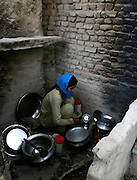 A young woman prepares food in an open kitchen in Khairo Dero village, in Larkana, Pakistan, on Thursday, Jan. 24, 2008. Pakistan is seeking to sustain growth in a country where the government estimates a fourth of the population lives in poverty, or on less than a dollar a day.