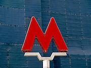 Das Logo der Moskauer Metro vor einer verhüllten Baustelle am Roten Platz in Moskau. <br /> <br /> Logo of the Moscow tube infront of a covered building.