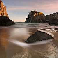 Sun setting over sandy beach with swirling water between rocks at Traigh Ghearadha beach, Lewis, Outer Hebrides, Scotland