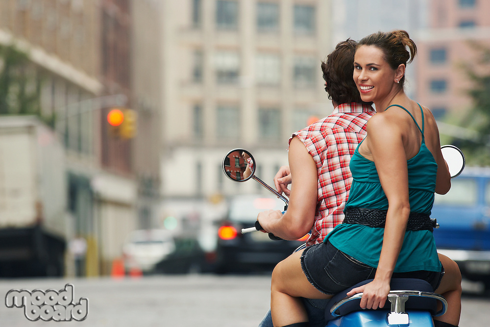 Couple riding on moped in street