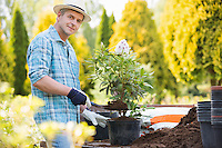 Portrait of confident man planting pot at garden
