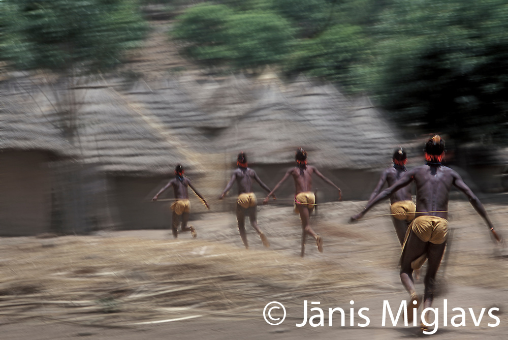 Boys in traditional clothes run through Iwol village as part of their six month initiation into manhood, Bedik tribe, Senegal, West Africa.