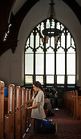 Ana Ulibarri of Mexico with fellow Up With People cast members wash down the pews at the Congregational Church Wednesday morning.  (Karen Bobotas/for the Laconia Daily Sun)