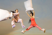 Two women having pillow fight mid-air outdoors