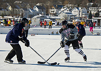 The Bitchin' Babes take on the Quincy Fighting Squirrlels during womens division pool play Saturday afternoon at the New England Pond Hockey on Meredith Bay.  (Karen Bobotas/for the Laconia Daily Sun)