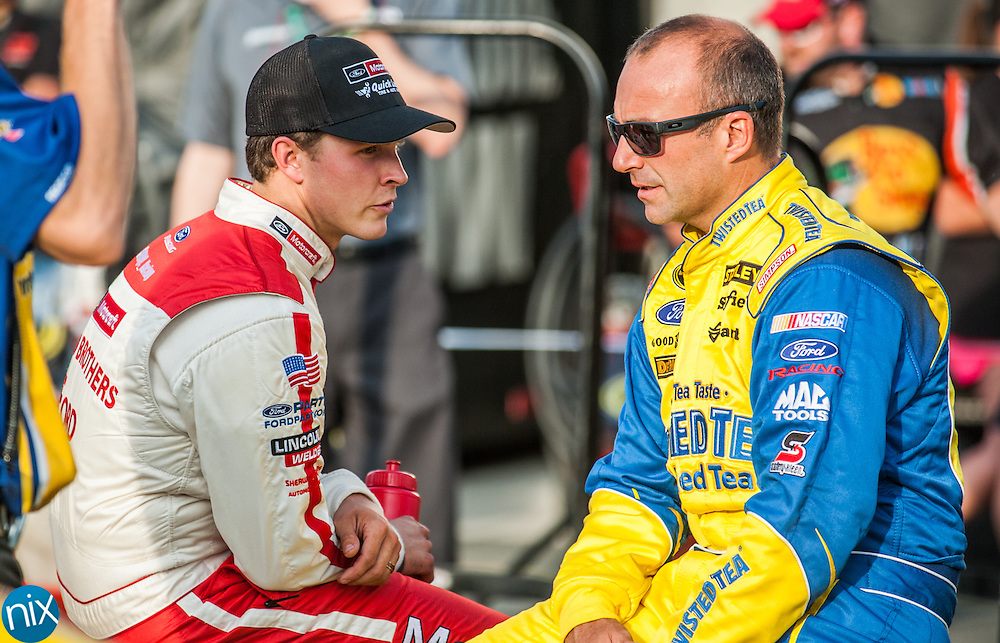 Trevor Bayne (21) and  Marcos Ambrose (9) talk prior to qualifying for the Coca-Cola 600 during Liftmaster Pole Night at Charlotte Motor Speedway on May 22, 2014.