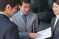 Businesspeople standing outside looking over documents