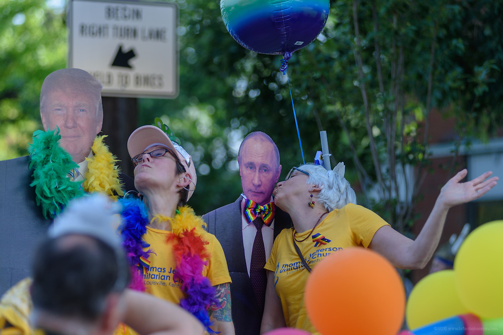 Joan Kofadimos and Rhonda Barnett of Thomas Jefferson Unitarian Church kiss cutouts of Trump and Putin for photos.<br /> The Lesbian, Gay, Bisexual, Transgender, and Queer (LGBTQ) community and their friends, family and supporters walked and lined Main Street from Floyd Street to the Belvedere for the Kentuckiana Pride Parade, Saturday, June 16, 2017 in Louisville, Ky. (Photo by Brian Bohannon)