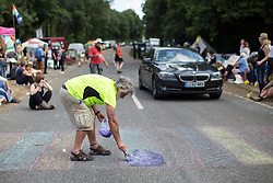 © licensed to London News Pictures. London, UK 03/08/2013. A man paints a zebra cross on a road as part of the protest against oil exploration in Balcombe, West Sussex enters its 10th day on Saturday, August 03, 2013, a day after energy company Cuadrilla began drilling at the site. Photo credit: Tolga Akmen/LNP