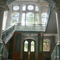 Grand entrance with large windows and staircase in old disused hospital