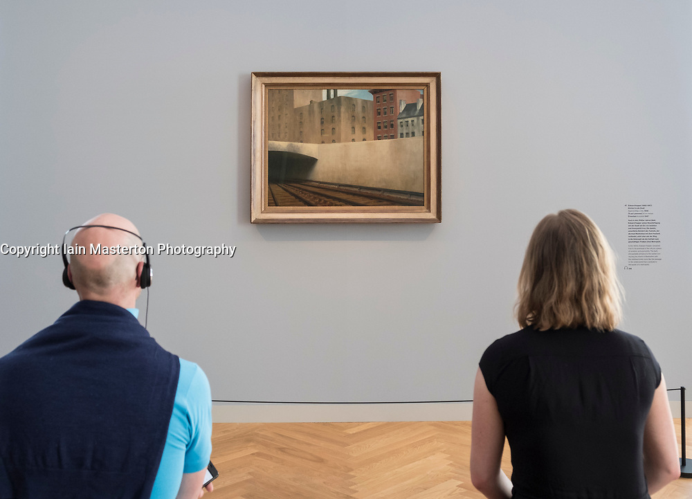 Visitors looking at painting  Approaching a City by Edward Hopper, at exhibition of American art , From Hopper to Rothko at the Barberini Museum in Potsdam , Germany . Editorial Use Only