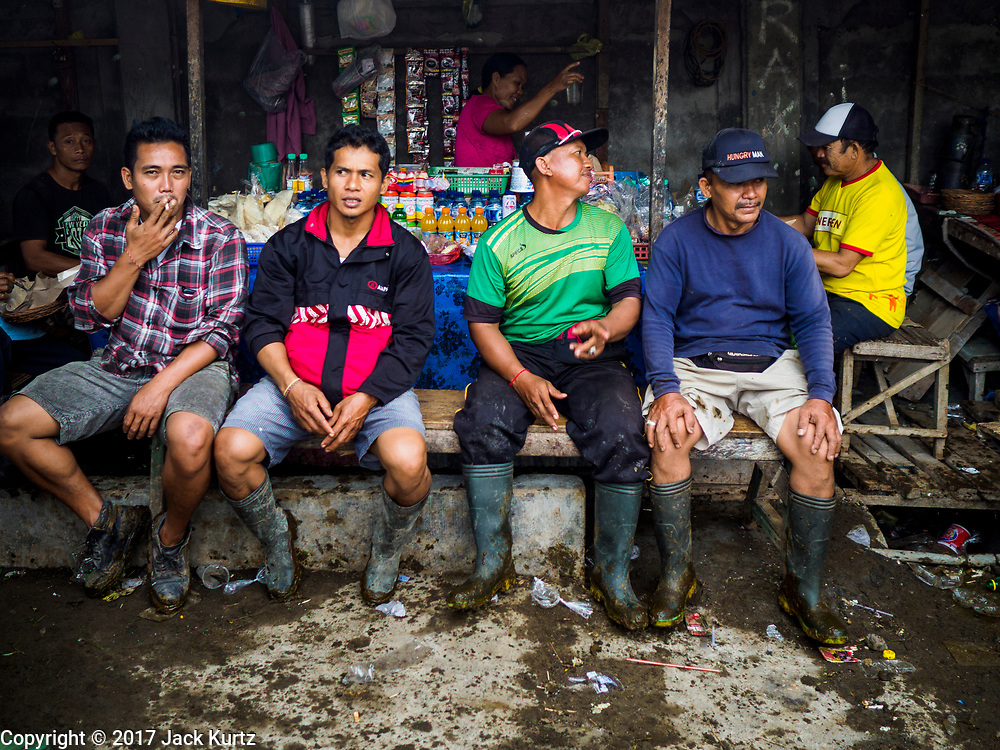"06 AUGUST 2017 - MENGWI, BALI, INDONESIA: Men eat their breakfast in a small ""warung"" (family owned restaurant or snack shop) in the livestock section of the  Bringkit Market in Mengwi, about 30 minutes from Denpasar. Bringkit Market is famous on Bali for its Sunday livestock and poultry market. Hundreds of the small Bali cows are bought and sold there every week. Bali's local markets are open on an every three day rotating schedule because venders travel from town to town. Before modern refrigeration and convenience stores became common place on Bali, markets were thriving community gatherings. Fewer people shop at markets now as more and more consumers go to convenience stores and more families have refrigerators.     PHOTO BY JACK KURTZ"