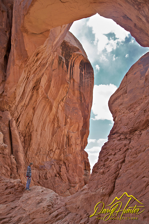 A visitor looks through Double Arch in Arches National Park of Moab Utah
