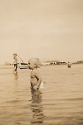 photograph of a little child standing in the water summer 1937