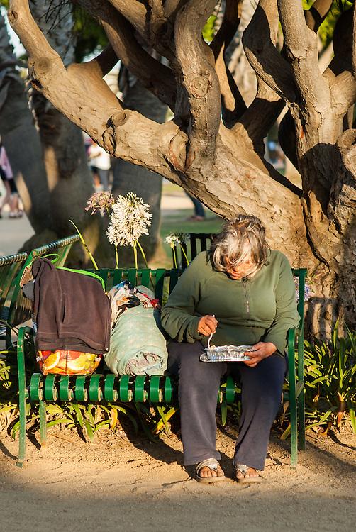 An homeless has dinner at the sunset, in Santa Monica, California.