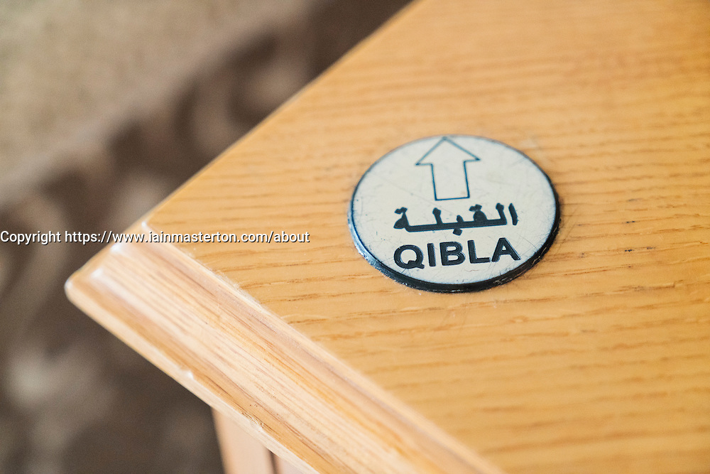 Qibla arrow on hotel table indicating direction of Mecca for prayer in the Middle East