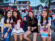 "23 DECEMBER 2018 - CHANTABURI, THAILAND: Girls wearing Christmas decorations eat snacks at the Cathedral of the Immaculate Conception's Christmas Fair in Chantaburi. Cathedral of the Immaculate Conception is holding its annual Christmas festival, this year called ""Sweet Christmas @ Chantaburi 2018"". The Cathedral is the largest Catholic church in Thailand and was founded more than 300 years ago by Vietnamese Catholics who settled in Thailand, then Siam.  PHOTO BY JACK KURTZ"