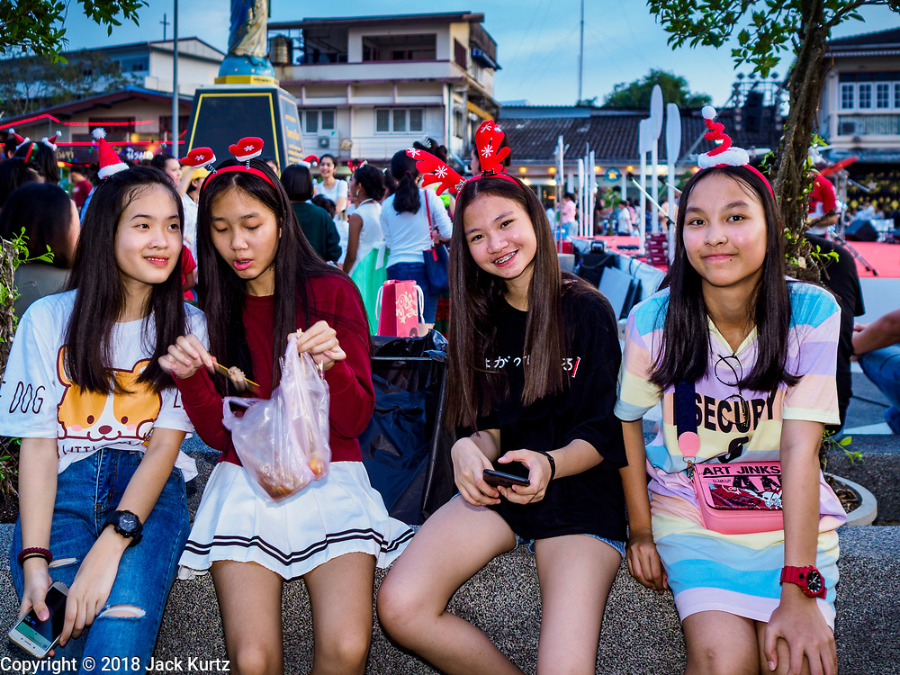 """23 DECEMBER 2018 - CHANTABURI, THAILAND: Girls wearing Christmas decorations eat snacks at the Cathedral of the Immaculate Conception's Christmas Fair in Chantaburi. Cathedral of the Immaculate Conception is holding its annual Christmas festival, this year called """"Sweet Christmas @ Chantaburi 2018"""". The Cathedral is the largest Catholic church in Thailand and was founded more than 300 years ago by Vietnamese Catholics who settled in Thailand, then Siam.  PHOTO BY JACK KURTZ"""