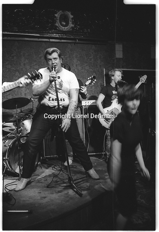 Singer in a rock band with woman dancing in a pub, Catford, South East London, London street photography in 1982. Tri-X
