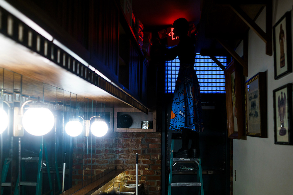 Washington, D.C. - November 19, 2016: Bad Saint server Shaheen Qureshi preps the restaurant on a ladder before Saturday night dinner, November 19, 2016.<br /> <br /> D.C. Filipino restaurant Bad Saint was recently named the second best new restaurant in America by Bon Appetite.<br /> <br /> <br /> CREDIT: Matt Roth for The New York Times<br /> Assignment ID: 30199012A