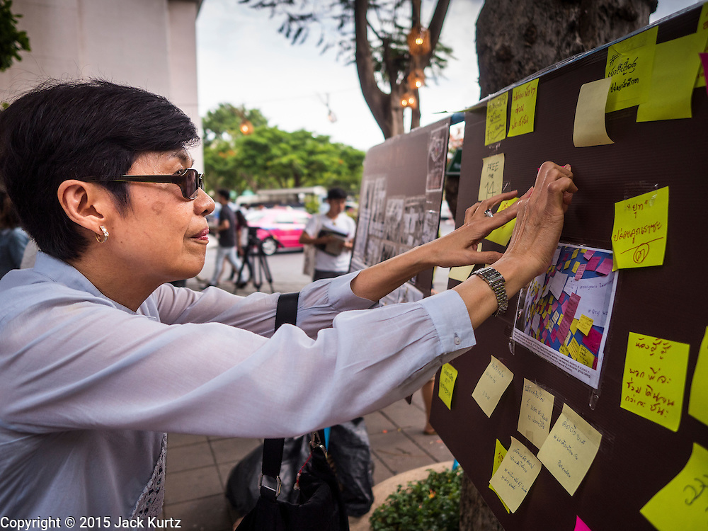 "06 JULY 2015 - BANGKOK, THAILAND: A person puts a ""Post It"" note in support of arrested university students during a protest at Thammasat University. More than 100 people gathered at Thammasat University in Bangkok Monday to show support for 14 students arrested two weeks ago. The students were arrested for violating orders against political assembly. They face criminal trial in military courts. The students' supporters are putting up ""Post It"" notes around Bangkok and college campuses up country calling for the students' release.   PHOTO BY JACK KURTZ"