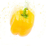 Exploding Yellow Bell pepper (Capsicum annuum) on white background