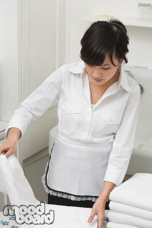 Female housekeeper folding white towel
